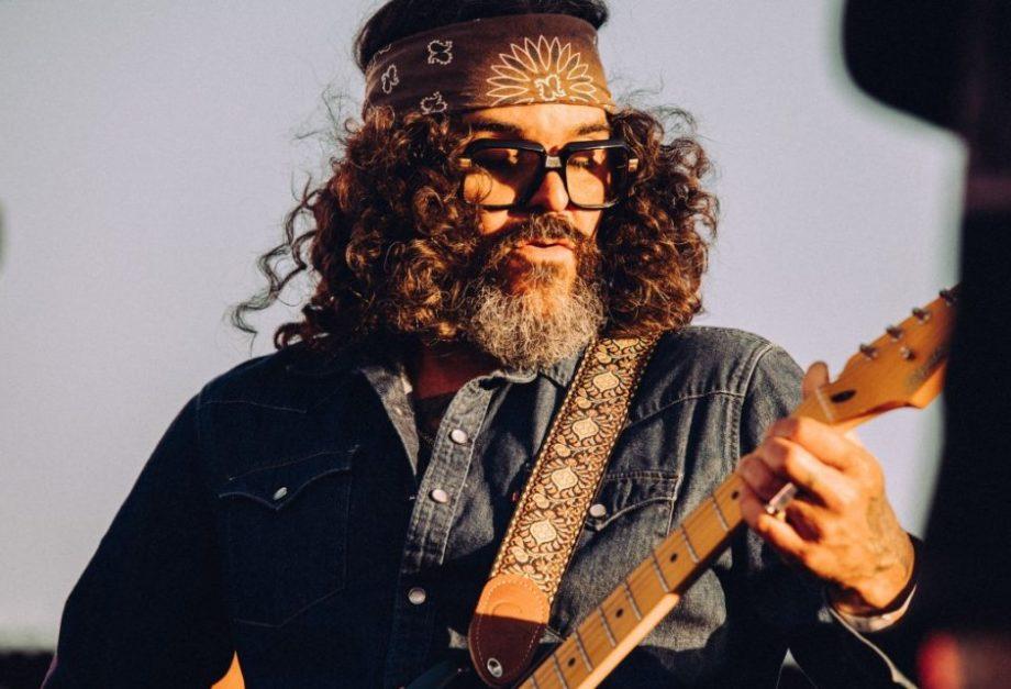 Guitarrista Adam Cohen toca guitarra com céu azul atrás